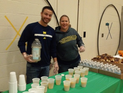 Two teachers pose for the camera as they continue to full up juice cups.