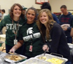 Three teachers smile bright as they hold up some scrambled eggs and pancakes.