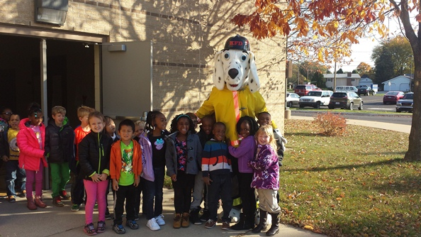 Brookwood students gather around the Firefighter's mascot. A dalmatian dog wearing a yellow shirt, orange tie and a hat.