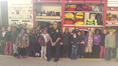 Students stand with a firefighter beside his truck. We can see all the equipment the fire fighters use!