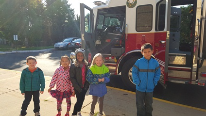 Five students stand close to the fire truck.