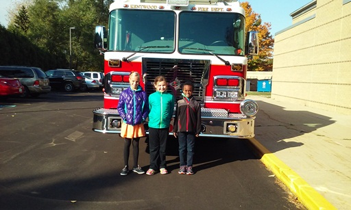 Three girls stand in front of a fire truck on a sunny day.