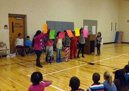During a student's speech, she has friends hold up colorful signs.