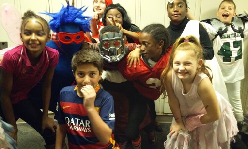 A group of kids smile as they pose in costume. A fairy, soccer and football stars, cheerleader, star lord, and a few others.