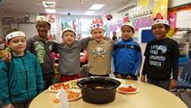Kids in Mrs. Dykstra's class wrap their arms around each other as they look at their meal.
