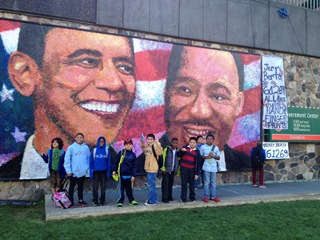 Students stand in front of a mural that shows Obama and Martin Luther King Jr on it.
