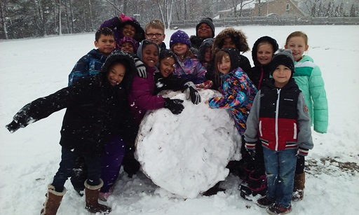 Students happily gather around a large snowball.