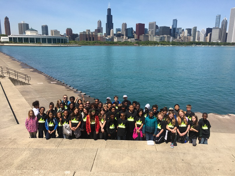 The fifth graders stand with the Chicago skyline behind them.
