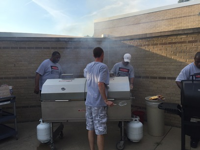 A few dads standing around a large grill while cooking up some delicious food!