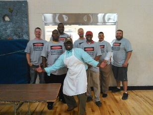 A group of dads stand together with the Principal to show off their dad's grilling shirts.