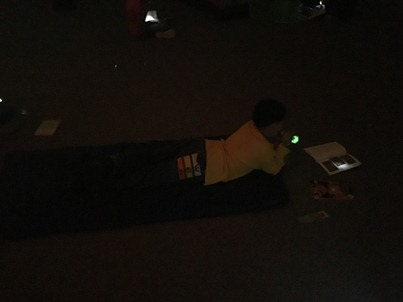 A boy lies on a sleeping bag while using a flashlight to read his book.