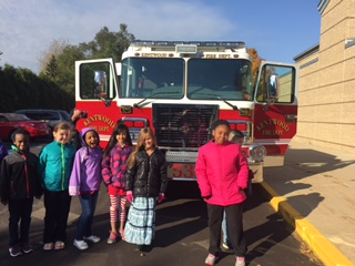 Six students pose happily in front of the fire truck.