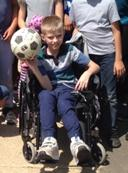 A student, happily holding a soccer ball.